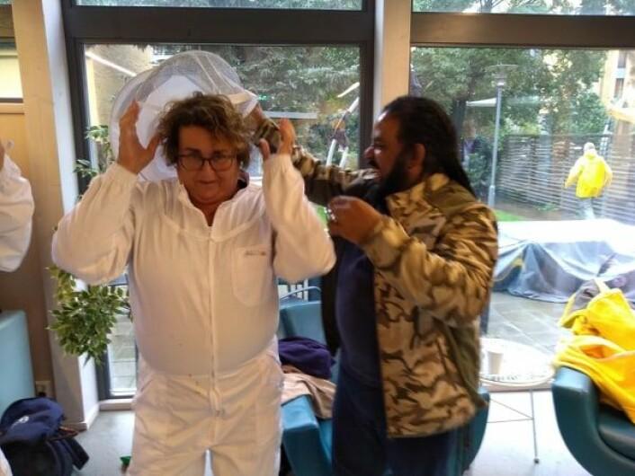 Matminister Olaug Bollestad (KrF) får hjelp av Omar til å ta på birøkterdrakt. Foto: Arnsten Linstad