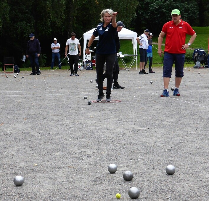 <em>Gunvor Berge kaster presist. </em>Målet er å kaste metallballene nærmest mulig en mindre kule av tre. Den som først oppnår 13 poeng har vunnet. Foto: Åsmund Berge