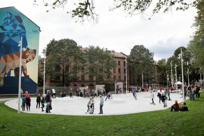 Den asfalterte plassen var tidligere et skummelt sted for barna på Lakkegata. Nå har de tatt over den nye skolegården og fyller den med lek. Illustrasjonen på veggen til venstre, utført av Ricardo Ten Colombo, er det beboerne i blokka som har valgt ut. Foto: Sverre Chr Jarild
