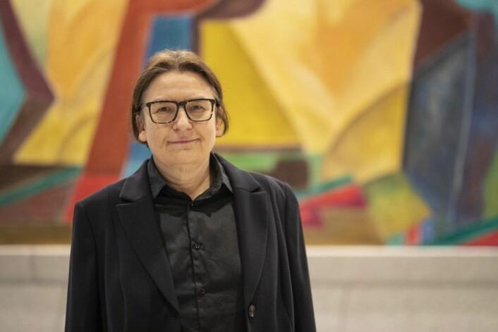 Ragnhild Hennum, dekan ved Det juridiske fakultet, foran et av kunstverkene i Domus Juridica. Foto: Olav Helland