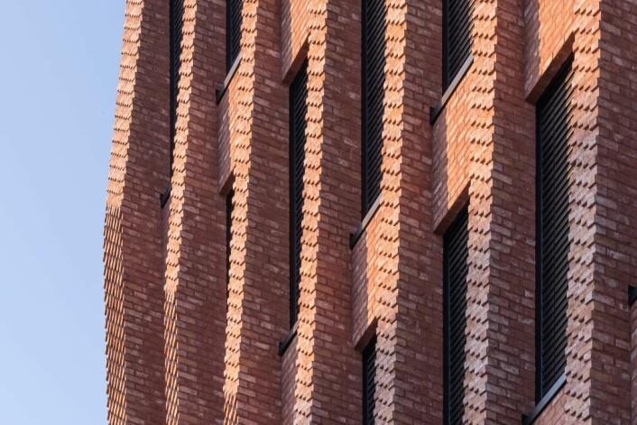 En ung arkitekt fra Mad fant et «system» for teglsteinen som endte i to spesialstein som er designet og gir det spillet man ser i fasaden i dag. Veidekkes egne murerlag har håndgjort hele fasaden, en jobb som tok 4-5 ganger så lang tid som det som er vanlig i dag. Foto: Mad arkitekter / Kyrre Sundal