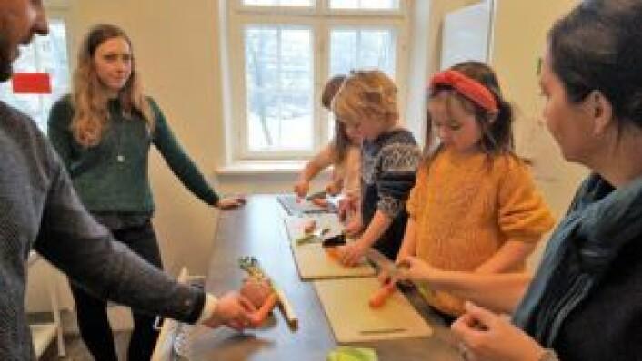 De små kokkene lar seg ikke hefte av de voksne (her Lars Magnus Ottersen, Christine Spidsberg og Anne Christine Kroepelien) som prater om prosjektet. Foto: Tarjei Kidd Olsen