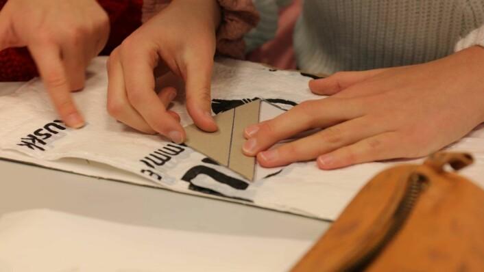 MÅLES OPP: En trekant i papp brukes til å skjære til plastposene. Foto: Elisabeth Tobiassen Faane