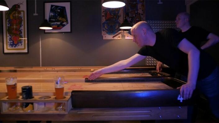 To kompiser konkurrerer mot hverandre i shuffleboard på Tilt, og shuffleboard-bordet har selvfølgelig egen ølglassholder. Foto: Thor Langfeldt