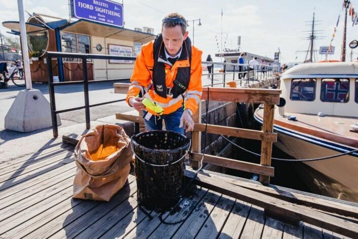 Oslo Havns dronefører og søppelinnsamler, Edvin Wibetoe, med den flytende søppelbøtten (også kalt portbin). Foto: Geir Anders Rybakken Ørslien