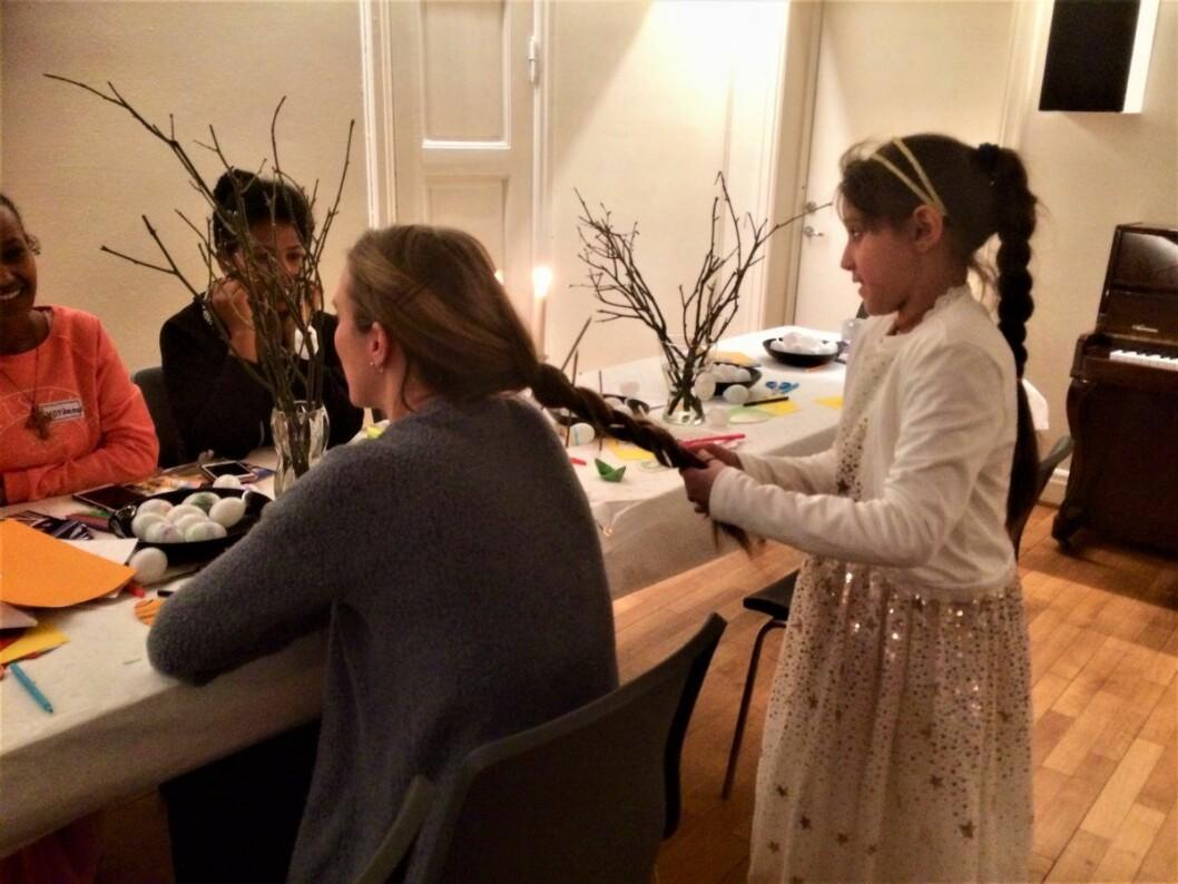 Denne lille jenta fletter håret til en av de frivillige som har møtt opp på et kvinnetreff for flyktninger i regi av Uranienborg menighet. Treffet finansieres med frivillighetsmidler fra Bydel Frogner. Foto: Uranienborg menighet