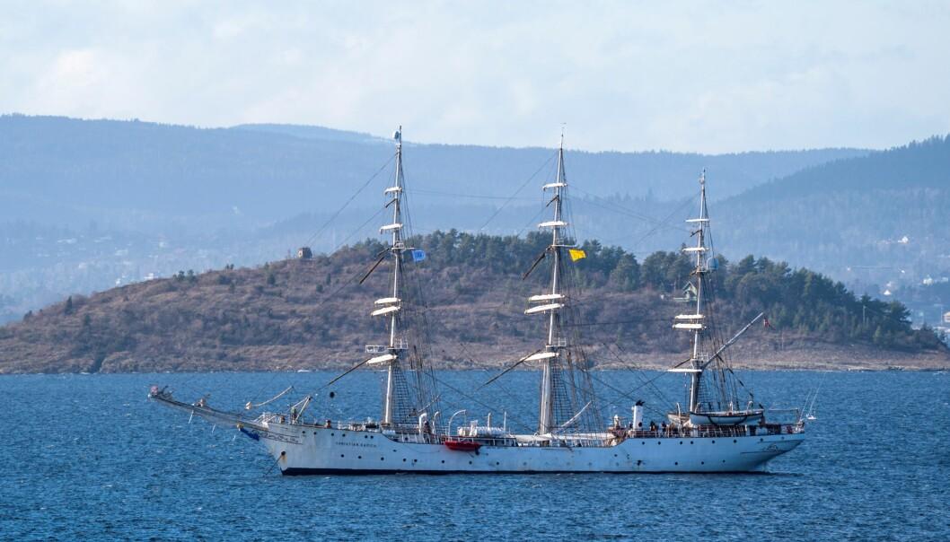 Midt mellom øyene i Bunnefjorden ligger skoleskipet Christian Radich. I den midterste masten skimtes det gule karanteneflagget som varsler andre skip at det kan være smittsom sykdom ombord.