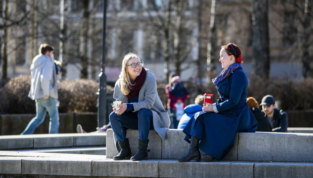 Vennene Marianne Hem Eriksen (t.v.) og Mari Malmer holder litt ekstra avstand mellom seg når de nyter sola på Birkelunden på Grünerløkka.