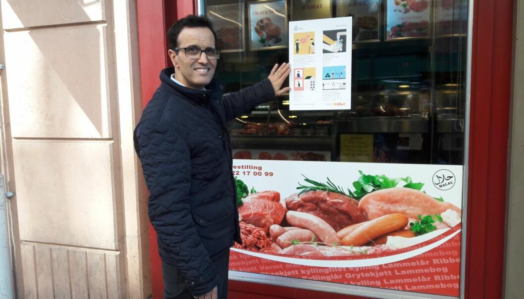 Yassine Arakia med plakaten i vinduet hos Grønlands torg kjøtt