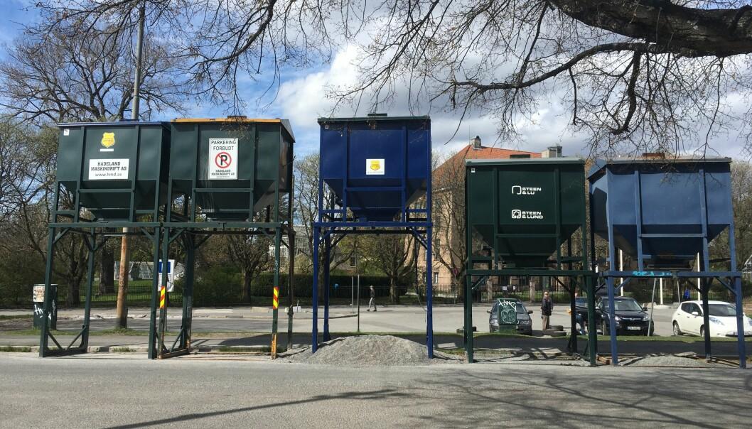 Fem sandsiloer står svært synlig plassert foran Botanisk hage. De tre grønne tilhører bymiljøetaten.