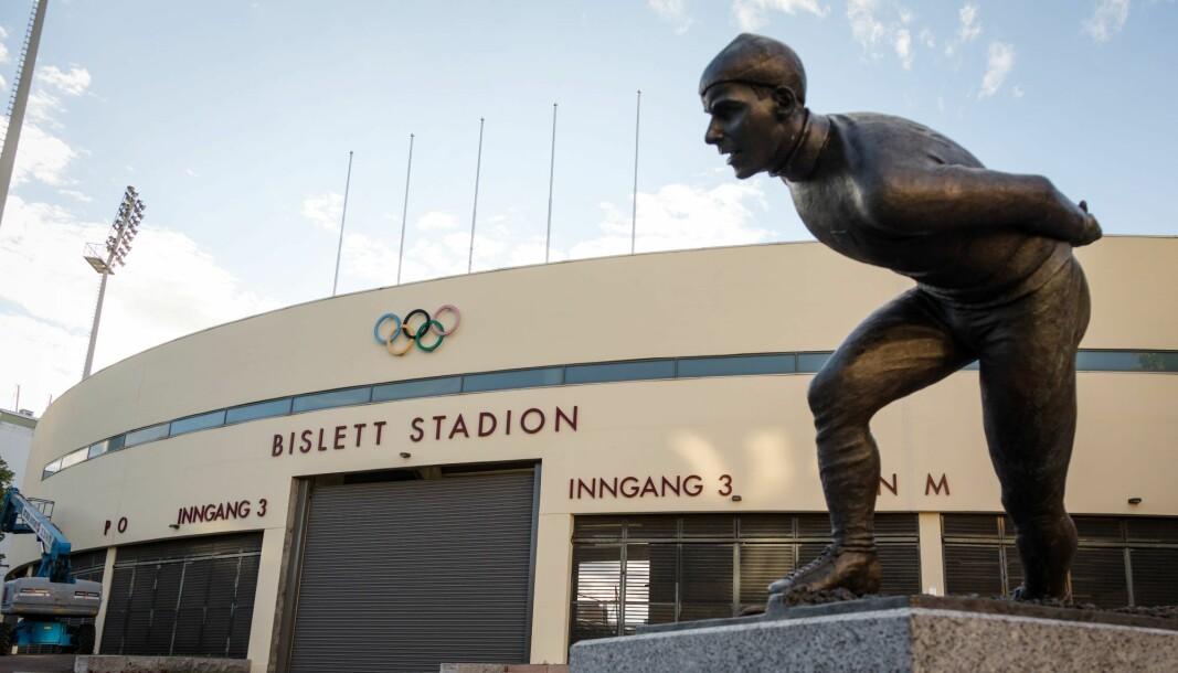 """15 år gamle Nye Bislett stadion, her med opprinnelig skilting og store bokstaver, føres opp på gul liste over verneverdige bygg. I forgrunnen statuen av Knut """"Kuppern"""" Johannesen"""