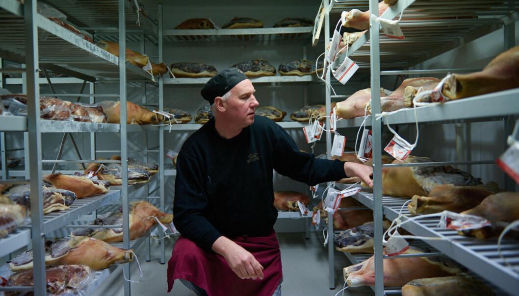 Daglig leder Jan Strøm-Larsen viser frem skinkene på lagerrommet.