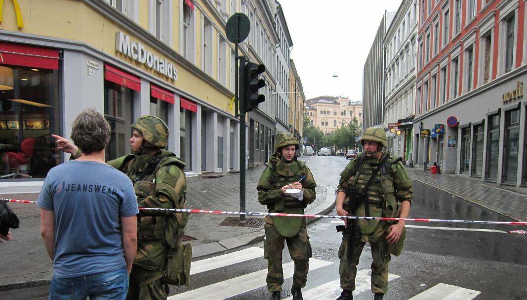 Dagen etter terrorangrepet, 23. juli 2011, der hvor Pløens gate møter Storgata. Soldater ble utplassert i Oslos gater for første gang siden 2. verdenskrig etter angrepet. Den knuste urskiven i Møllergata 19 ved Youngstorget skimtes i bakgrunnen. Butikker så langt unna som Gunerius fikk rutene knust på grunn av trykkbølgene fra eksplosjonen i regjeringskvartalet.