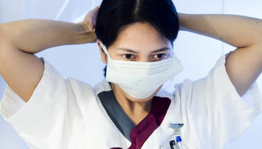 Helsefagarbeider tar på seg munnbind. Hygienetiltak. Illustrasjonsbilde. Foto: Heiko Junge / SCANPIX NB Modellklarert.