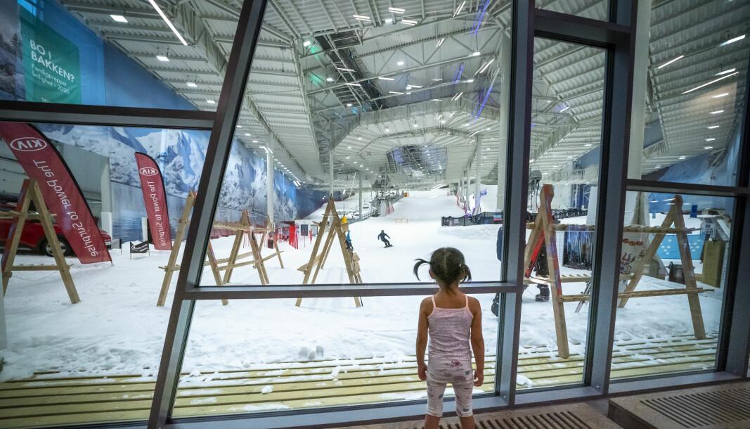 En liten jente kikker gjennom glassvinduene og inn i skianlegget, som holder mellom 2 og 4 minusgrader.