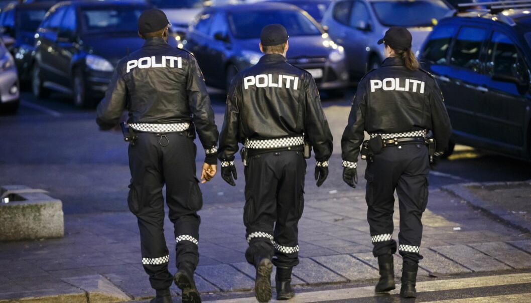 Tre politifolk patruljerer gatene.