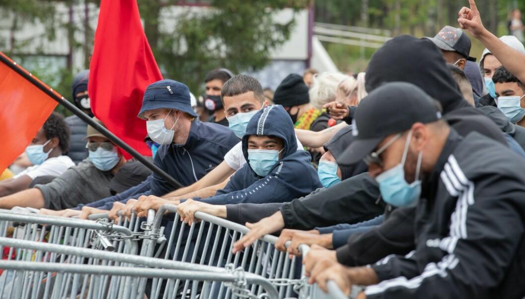 Motdemonstranter røsker i sperringene politiet har satt opp for å beskytte Sian.