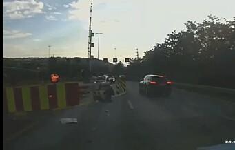 MC-føreren filmes fra kameraet i en bil. Plutselig SMELLER det. Utrolig nok går det bra. Se videoen