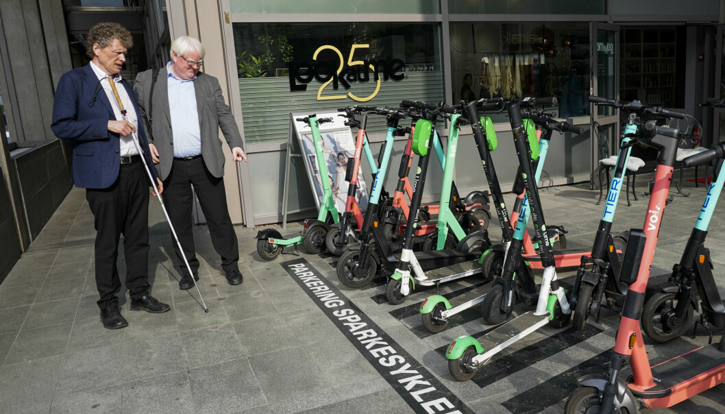 Blindeforbundets leder Terje Andre Olsen (t.h) og leder for samfunnskontakt Sverre Fuglerud ved parkering for elsparkesykler i Akersgata. De vil at elsparkesykler bare skal kunne parkeres på oppmerkede plasser.