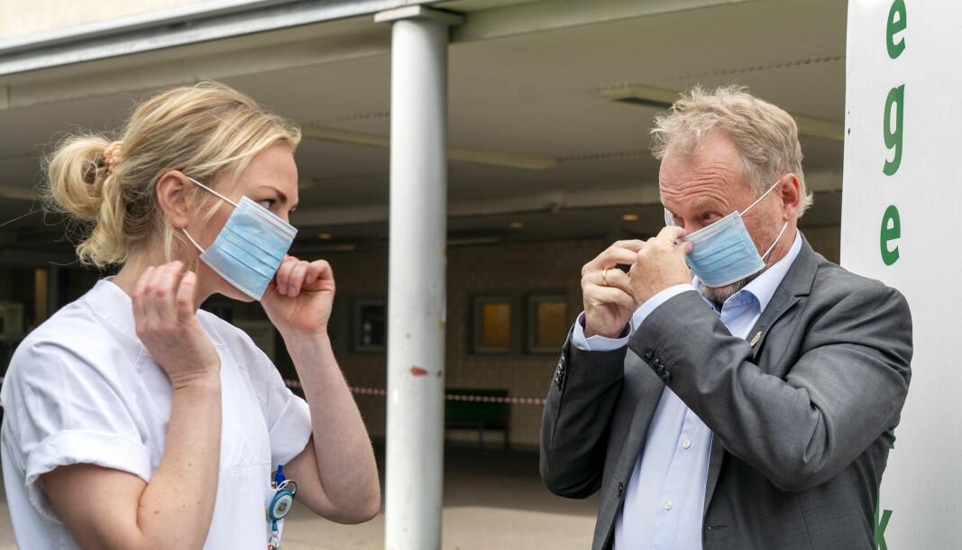 Byrådsleder Raymond Johansen tar på seg munnbind sammen med sykepleier Ingrid Frøshaug Forbord under besøk på koronateststasjonen utenfor Aker legevakt.