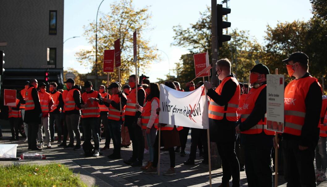 Streikende vektere i streikevester og med store plakater utenfor NHO.