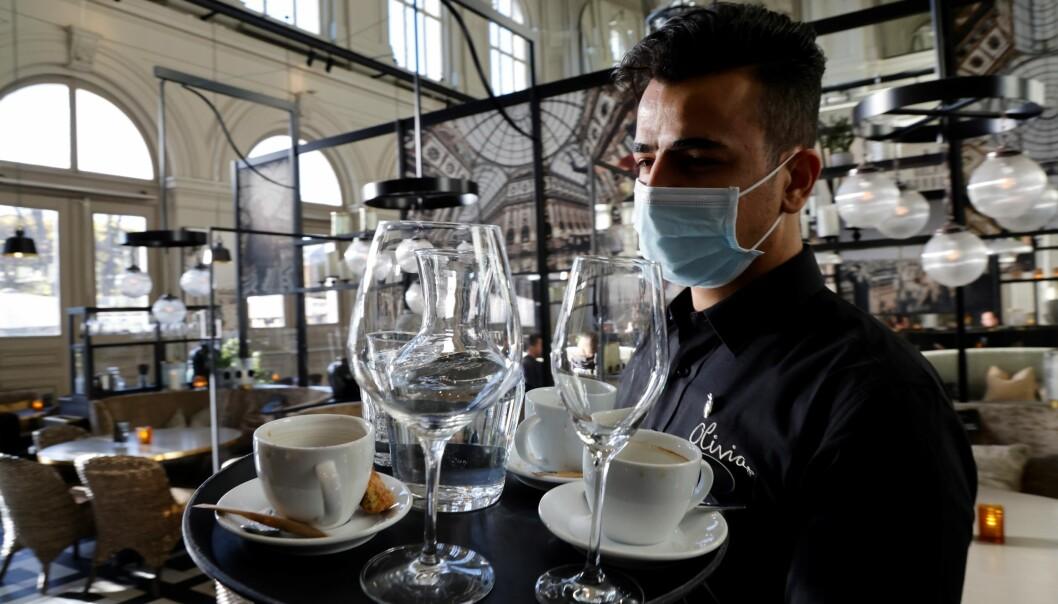 Servitør Firas Aljabli på Olivia restaurant bruker munnbind når han serverer. Fra torsdag denne uken er det påbud om munnbind for kelnere og servitører.