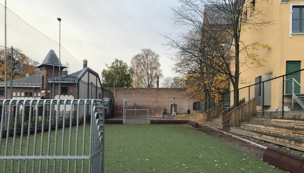 Skolens hovedbygninger ligger bak muren bakerst i bildet. Den lille ballbanen er også en del av skoleanlegget.