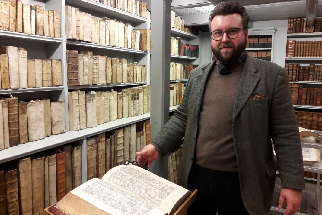 Samlingsforvalter Ernst Hugo Bjerke med ordboka skolen fikk i gave til elevenes benyttelse i 1663. Boka er lenket fast, slik giveren forlangte.