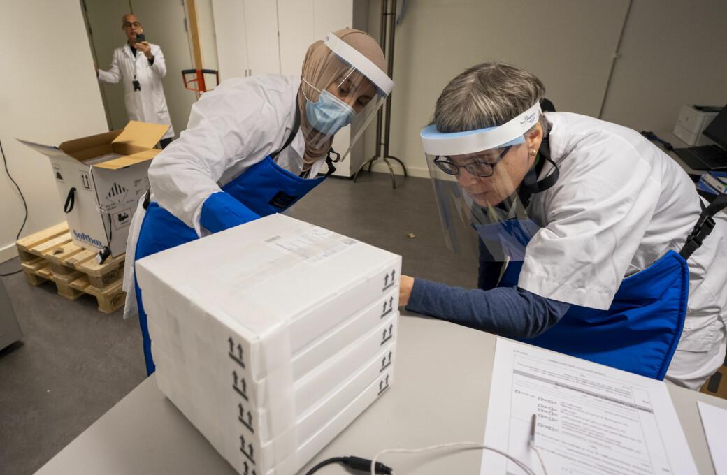 Farmasøyt Ellen Bergh (t.h), avdelingsleder Samira Benaissa mottar den første leveransen til Norge med 9.750 doser av koronavaksinen, utviklet av Pfizer og Biontech. I bakgrunnen tar Jalil Djahromi bilder av den historiske pakken.
