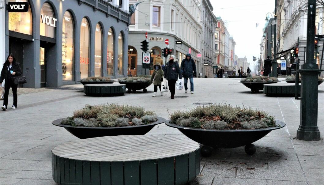 De midlertidig blomsterkassene skulle vært erstattet av permanente terrorbarrierer i 2018. Nå blir de stående i minst ett år til.
