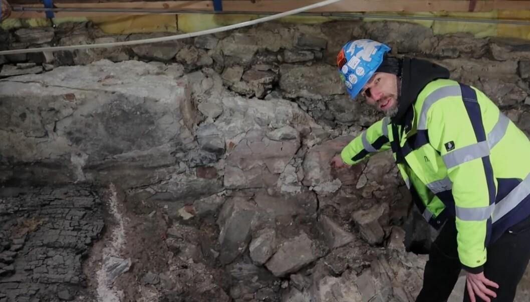 Håvard Hegdal, arkeolog i Norsk institutt for kulturminneforskning, viser fram sprekkdannelser i muren under Saxegaarden.