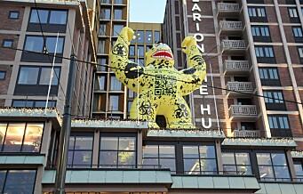 Et gedigent, gult godzilla-monster lyser mot Jernbanetorget fra hotelltaket på The Hub. Her er hvorfor
