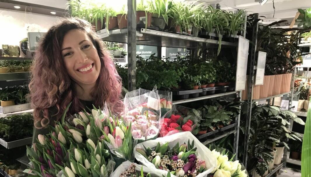 Sarah Stenholm er daglig leder for Mester Grønns butikk i Sandakersenteret. Sarah har tatt av seg munnbindet et øyeblikk, for å vise at hun smiler. - Nå gir vi bort alle de siste avskårne blomstene, slik at andre kan få glede av dem.