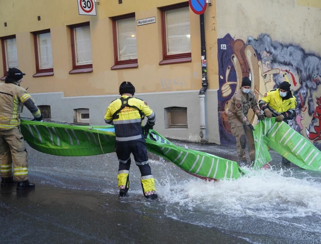 Mannskaper fra brann- og redningsetaten forsøkte å få kontroll på store vannmasser etter lekkasjen søndag morgen.