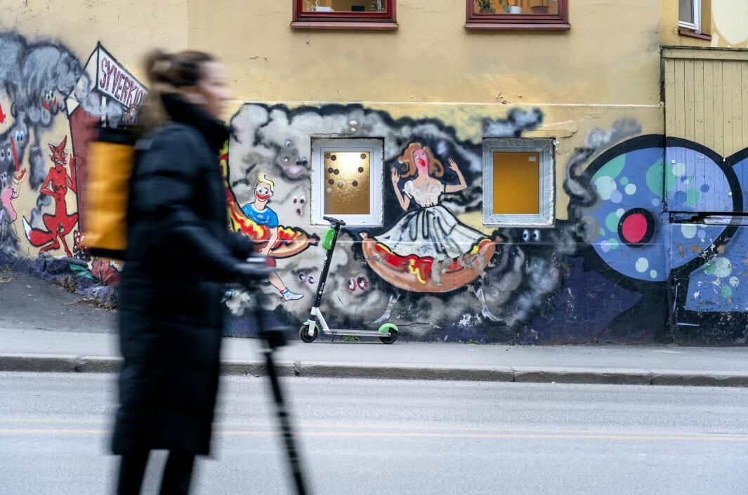 En elsparkesykkel henslengt på hjørnet av Maridalsveien og Waldemar Thranes gate på grensen mellom bydel Grünerløkka og bydel Sagene. Veggmaleriet er sprayet av Oslo-kunstneren Vanessa Baird. Den berømte pølsebua Syverkiosken ligger utenfor bildekanten. Foto: Gorm Kallestad / NTB