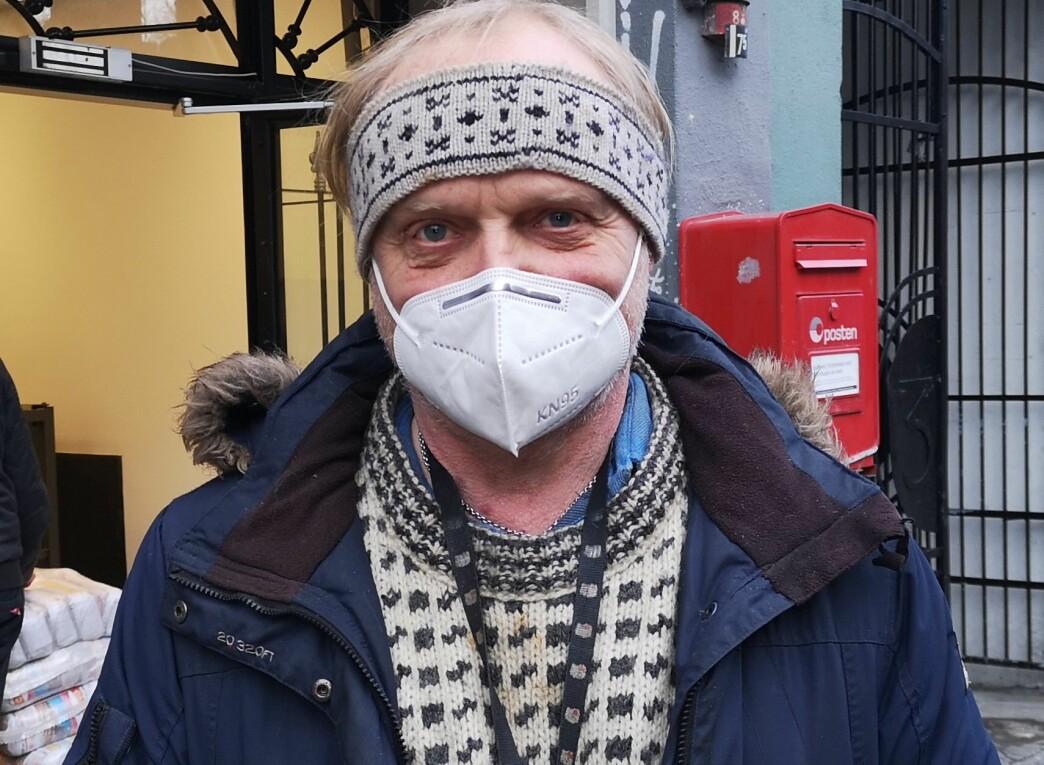 Styreleder på fattighuset i Oslo, Sverre Rusten, med masken på foran inngangen til Fattighuset.