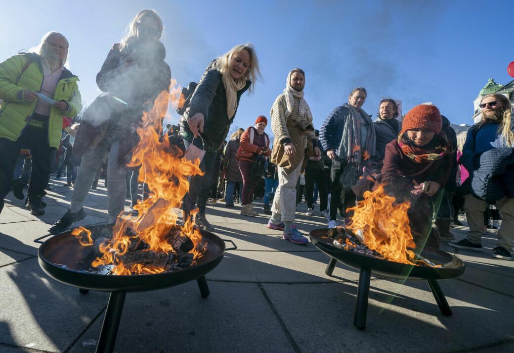 Koronaskeptikere brenner munnbind under en demonstasjon foran Stortinget lørdag ettermiddag.