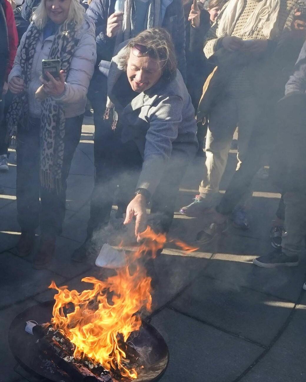 Svein Østvik, også kjent som Charter-Svein, brenner munnbindet sitt under koronaskeptikernes markering utenfor Stortinget.
