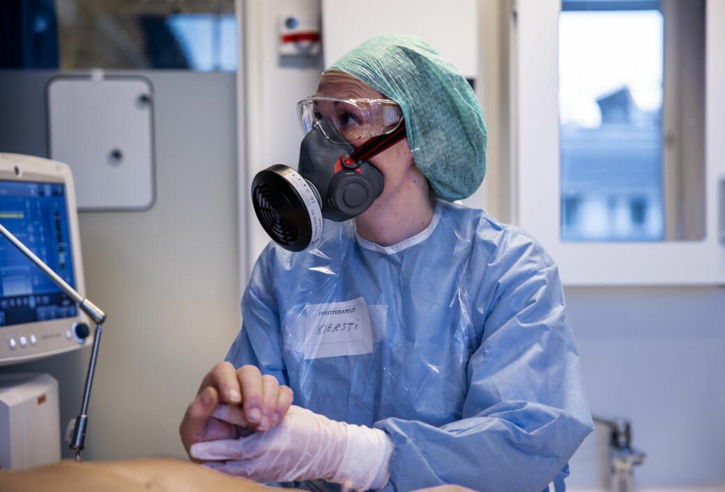 OUS har hatt ti koronadødsfall hittil i april. Her holder fysioterapeut Kjersti Bakke hånden til en av covid-pasientene som var innlagt i november i fjor.