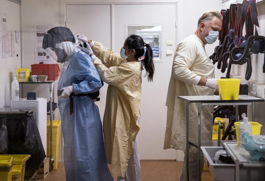 19 år gamle Catarina Anabelle Redish ( i midten) hjelper kolleger ved OUS Rikshospitalets korona-enhet med av og påkledning.