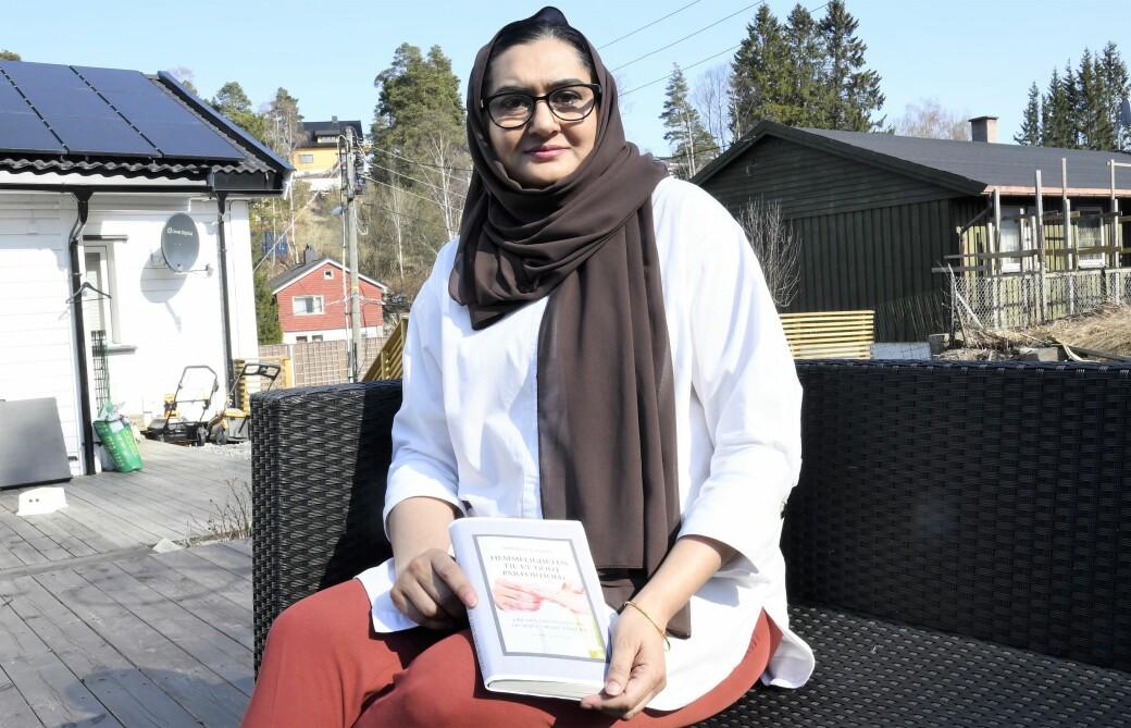 Sammia Naz Zaeem (45) på terrassen hjemme på Stovner med boka