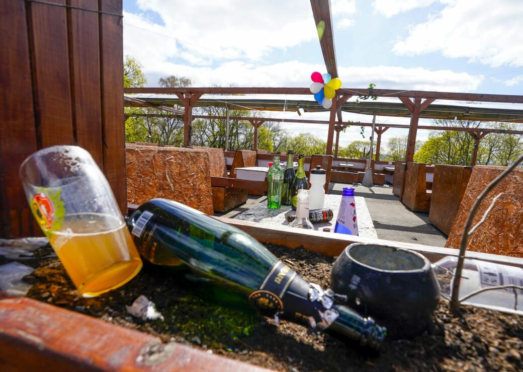 Vinflasker, spritflasker, ølbokser og et halvfullt halvlitersglass med ubestemmelig innhold ved den stengte uteserveringen på St. Hanshaugen søndag formiddag.