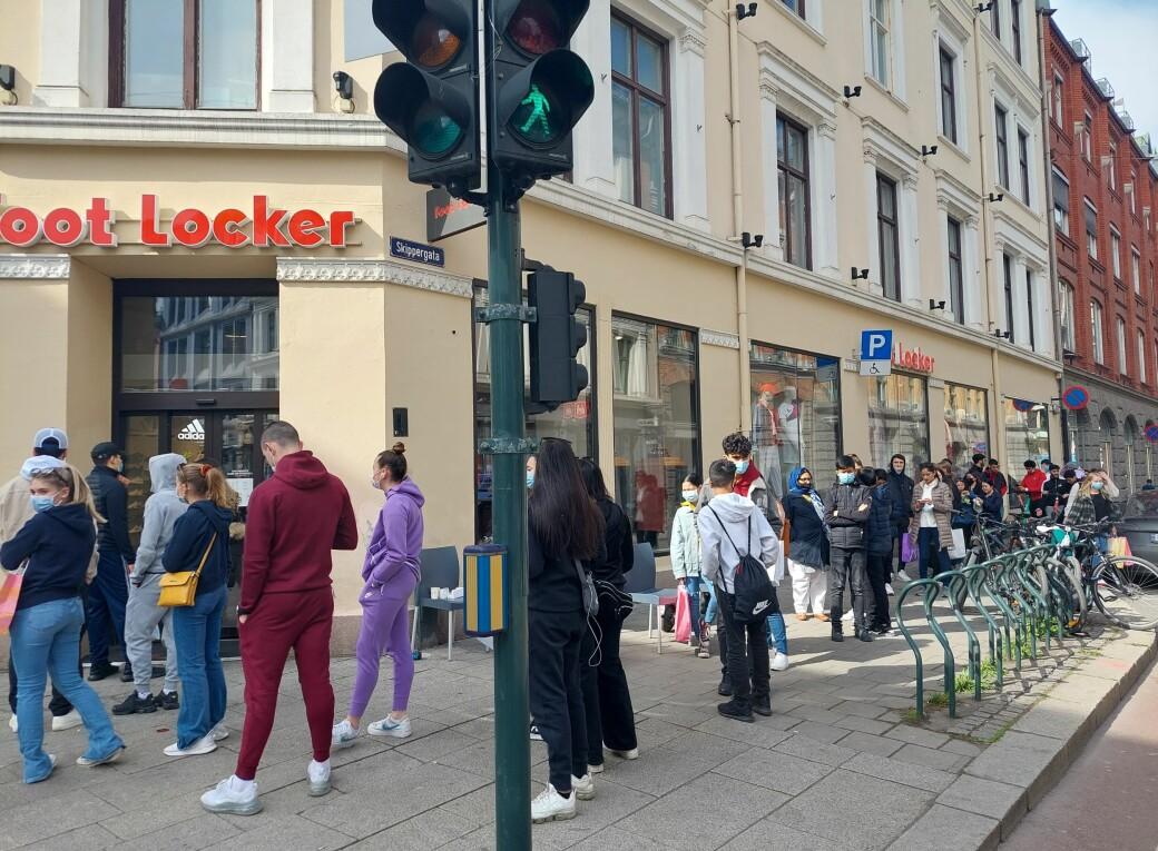 Folk sto i kø fra Skippergata og til inngangen til Foot Locker på hjørnet ved Karl Johans gate. Det er butikkens størrelse som avgjør hvor mange kunder som kan være inne samtidig.