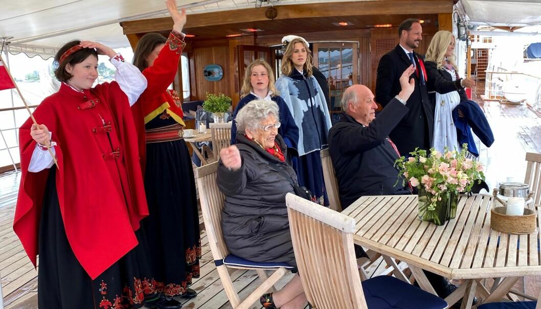 Dronningen knipser i det båtkortesjen fra Oslo seilforening passerer: Fra v. Maud Angelica Behn, prinsesse Märtha Louise, prinsesse Astrid, Emma Tallulah Behn, Leah Isadora Behn, kong Harald, kronprins Haakon og kronprinsesse Mette-Marit.