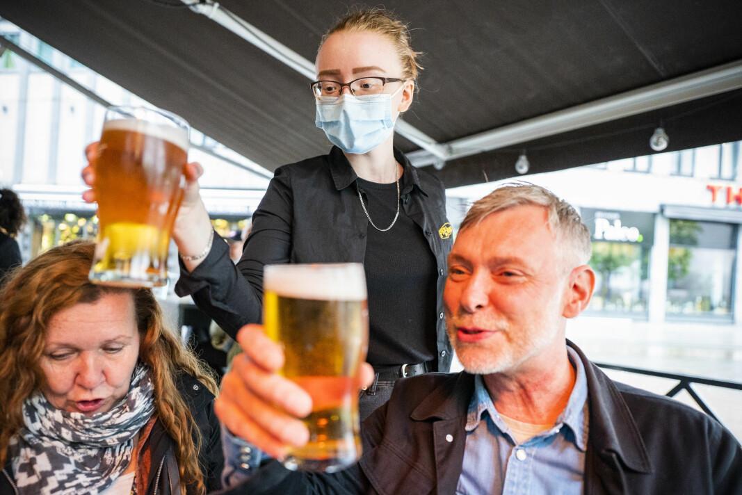 Servitør Ingrid Elise Bye har vært permittert i over et halvt år, men er endelig tilbake på jobb på puben Per på Hjørnet i Oslo sentrum. Her serverer hun øl til May Pedersen og Jan Øyvind Carlsen.