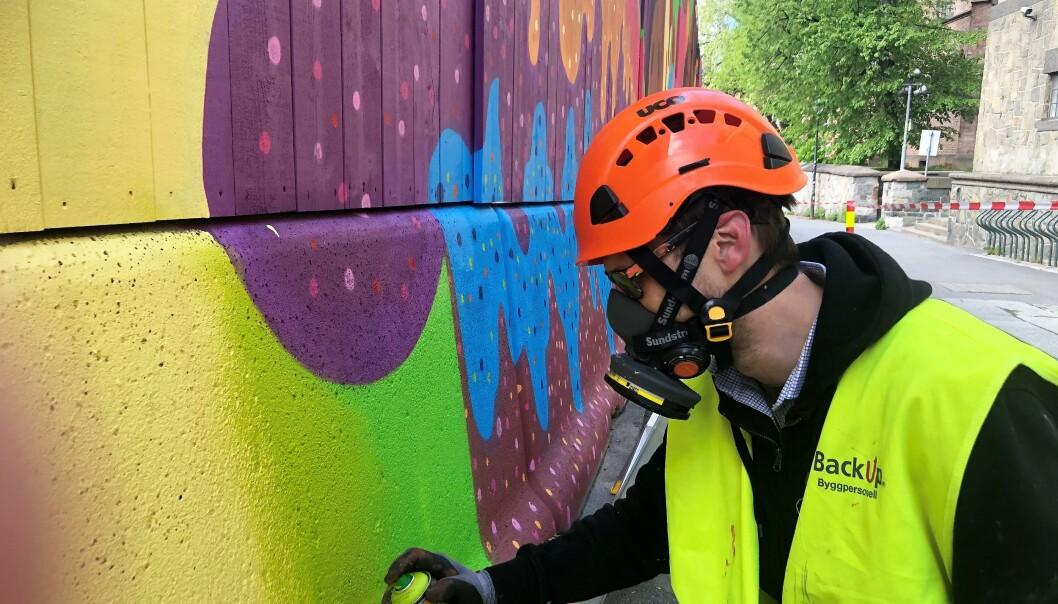 Espen Henningsen fargelegger regjeringskvartalet med en sprayboks.