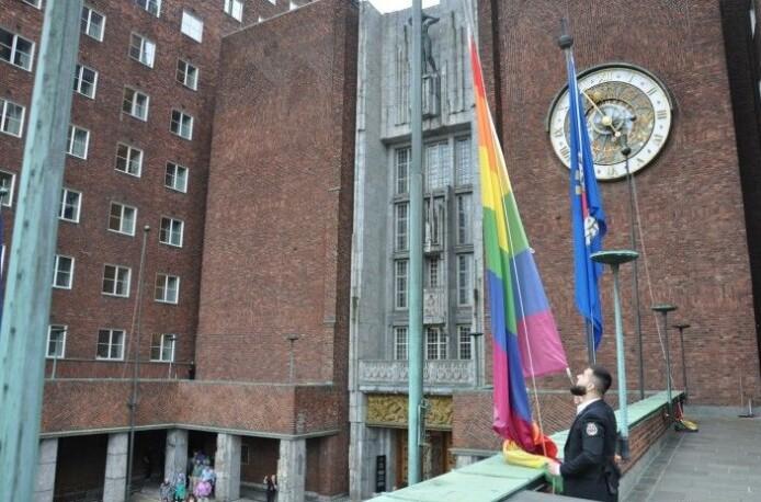En av rådhusvaktene heiste ett av mange Pride-flagg i 2019. Nå skal regnbueflaggene pryde Rådhuset dobbelt så lenge.