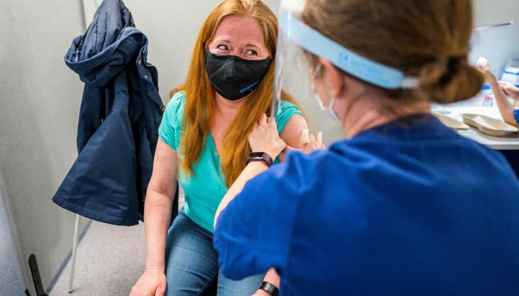Hilde Arnesen (52) ser takknemlig på sykepleier Åshild Skårland som setter på plaster etter sprøytestikket på vaksinesenteret i Bjerke bydel. Fortsatt er munnbind anbefalt i Oslo