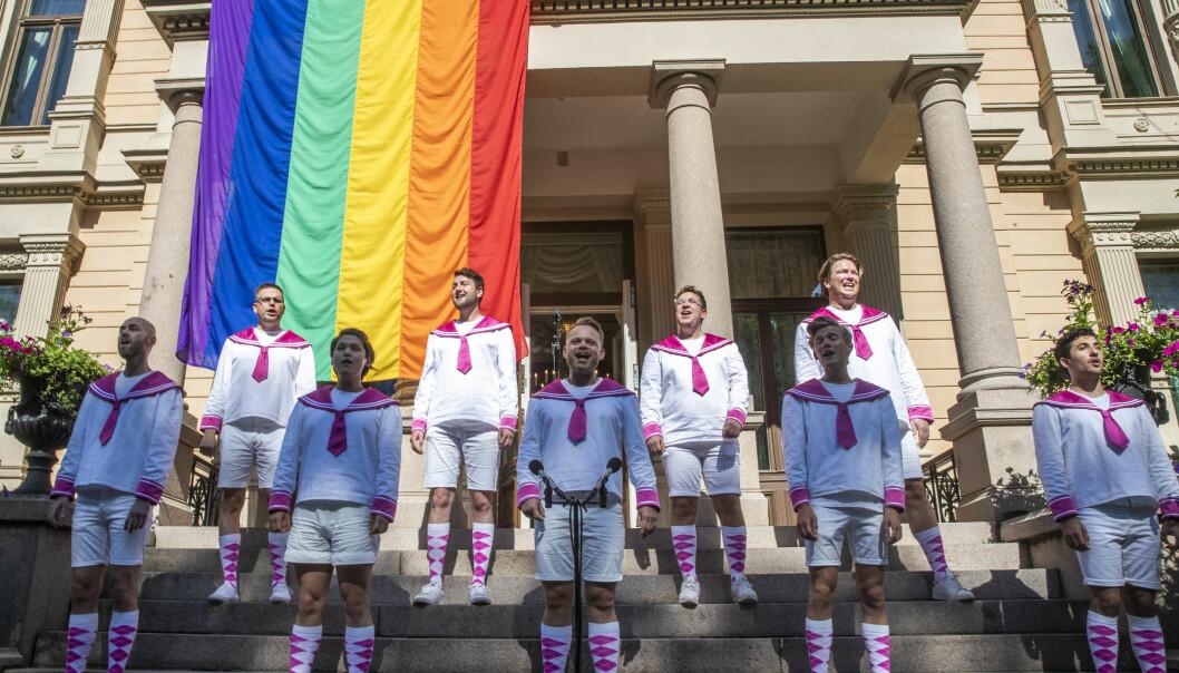 Oslo fagottkor synger mens regnbueflagget henges opp på regjeringens representasjonsbolig i Oslo i forbindelse med Oslo Pride i fjor.