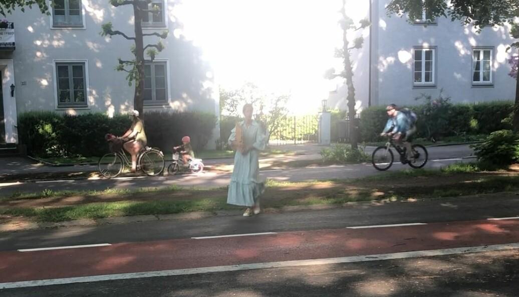 Et utsnitt fra videoen som viser foreldre og barn som sykler på egne sykler